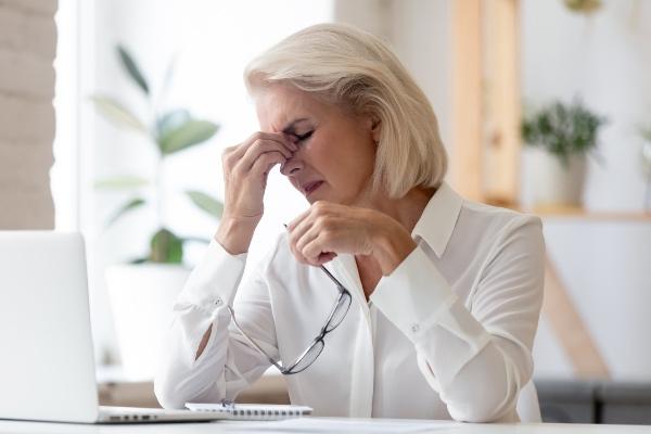neprijetni simptomi suhih oči pri starejši ženski v službi